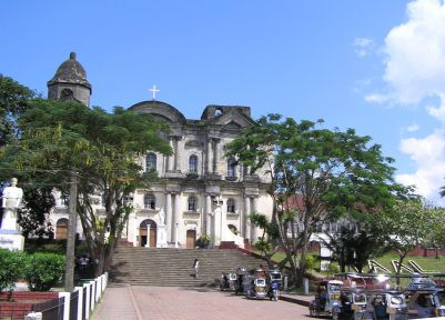 Trees and flowers surround the old, historic church in Taal
